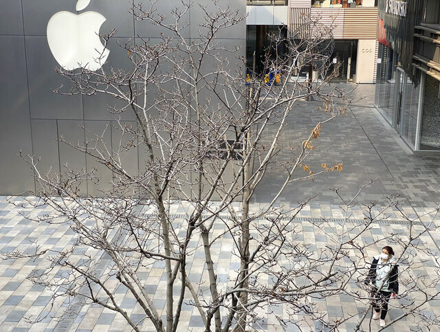 A woman wearing mask walks past the Apple store in an empty mall district in Beijing, China on Wednesday, Feb. 26, 2020. The tech giant Apple has reopened some of its stores in China but says the viral outbreak is starting to disrupt its supplies. (AP Photo/Ng Han Guan)