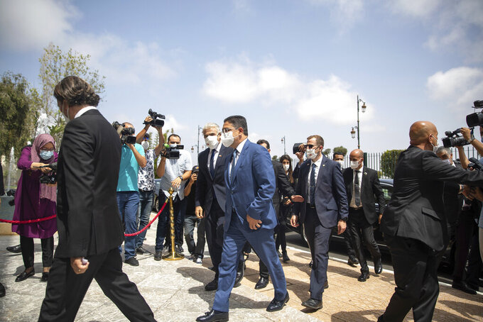 Moroccan Foreign Minister Nasser Bourita, centre right, welcomes Israeli Foreign Minister Yair Lapid, centre left, in Rabat, Morocco, Wednesday, Aug. 11, 2021. The Israeli Foreign Minister Yair Lapid is on an official visit to Morocco.  (AP Photo/Mosa'ab Elshamy)
