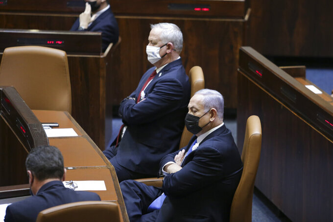 Israeli Prime Minister Benjamin Netanyahu, right, Defense Minister Benny Gantz, center, and other lawmakers attend the swearing-in ceremony for Israel's 24th government, at the Knesset, or parliament, in Jerusalem, Tuesday, April 6, 2021. The ceremony took place shortly after the country's president asked Netanyahu to form a new majority coalition, a difficult task given the deep divisions in the fragmented parliament. (Alex Kolomoisky/Pool via AP)