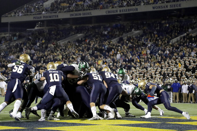 Tulane quarterback Justin McMillan, second from right, dives into the end zone for a touchdown against Navy during the second half of an NCAA college football game, Saturday, Oct. 26, 2019, in Annapolis. Navy won 41-38. (AP Photo/Julio Cortez)