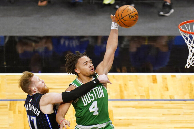 Orlando Magic forward Ignas Brazdeikis, left, fouls Boston Celtics guard Carsen Edwards (4) as he goes up for a shot during the second half of an NBA basketball game, Wednesday, May 5, 2021, in Orlando, Fla. (AP Photo/John Raoux)