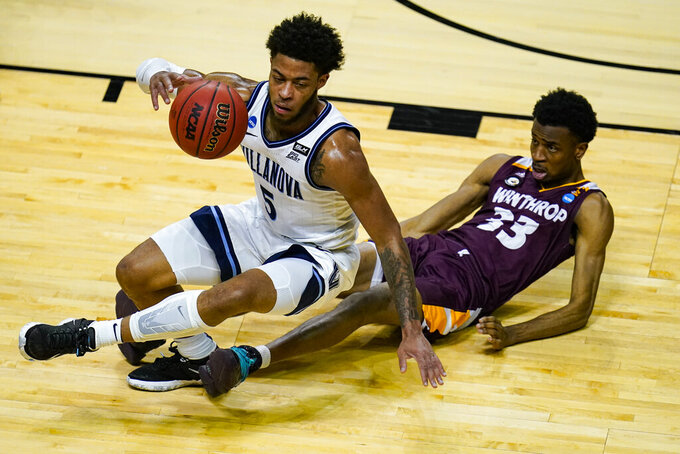Winthrop forward Chase Claxton (33) draws the charge from Villanova guard Justin Moore (5) in the first half of a first round game in the NCAA men's college basketball tournament at Farmers Coliseum in Indianapolis, Friday, March 19, 2021. (AP Photo/Michael Conroy)