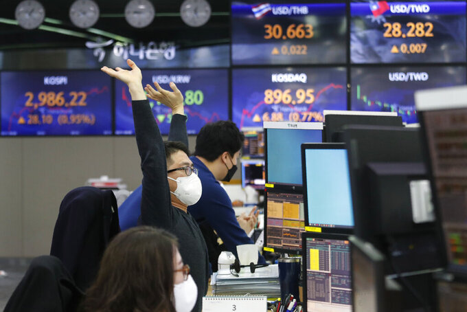 A currency trader stretches at the foreign exchange dealing room of the KEB Hana Bank headquarters in Seoul, South Korea, Thursday, March 11, 2021. Stocks climbed in Asia on Thursday after a key measure of inflation in the U.S. came in lower than expected, easing worries that price pressures could push interest rates higher. (AP Photo/Ahn Young-joon)