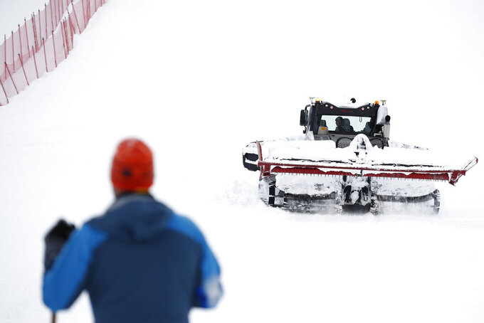 A snow plough is clearing snow on the course as the alpine ski, men's and women's World Cup downhill were cancelled due to weather conditions, in Lenzerheide, Switzerland, Wednesday, March 17, 2021. (AP Photo/Gabriele Facciotti)
