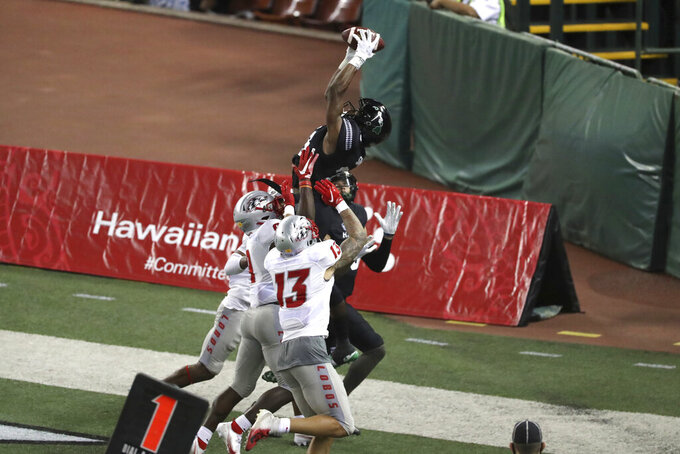 Hawaii wide receiver Jared Smart (23) leaps over New Mexico defenders catching the ball making a two-point conversion during the fourth quarter of an NCAA college football game, Saturday, Nov. 7, 2020, in Honolulu. (AP Photo/Marco Garcia)