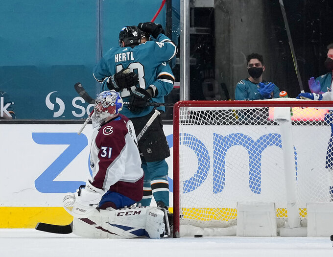 San Jose Sharks center Tomas Hertl (48) hugs a teammates after scoring a goal against Colorado Avalanche goaltender Philipp Grubauer (31) during the second period of an NHL hockey game in San Jose, Calif., on Wednesday, May 5, 2021. (AP Photo/Tony Avelar)