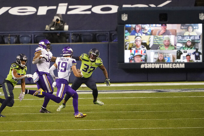 Fans are visible in the showtime cam behind the end zone as Minnesota Vikings' Adam Thielen (19) runs with the ball against the Seattle Seahawks during the second half of an NFL football game, Sunday, Oct. 11, 2020, in Seattle. (AP Photo/Ted S. Warren)