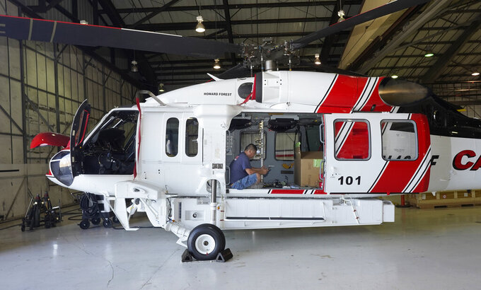 Avionics mechanic Mike Luong works on a Sikorsky Firehawk helicopter at the California Department of Forestry and Fire Protection's Sacramento Aviation Management Unit based at McClellan Airpark in Sacramento, Calif., Friday, July 23, 2021. Firefighters are trying to become smarter in how they prepare for the drought- and wind-driven wildfires that have become more dangerous across the American West in recent years, including by adding aircraft like the Sikorsky Firehawk helicopters or military surplus C-130 transport aircraft retrofitted to drop fire retardant. (AP Photo/Rich Pedroncelli)
