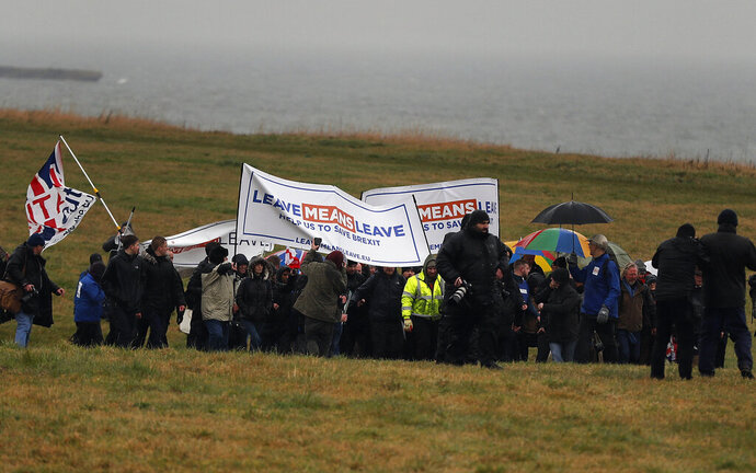 Protestors walk along the coastline at the start of the first leg of March to Leave the European Union, in Sunderland, England, Saturday, March 16, 2019. Hard-core Brexiteers led by former U.K. Independence Party leader Nigel Farage set out on a two-week
