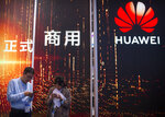 In this Oct. 31, 2019 photo, attendees use their smartphones near a Huawei booth at the PT Expo technology conference in Beijing. Chinese tech giant Huawei is racing to develop replacements for Google apps. U.S. sanctions imposed on security grounds block Huawei from using YouTube and other popular Google