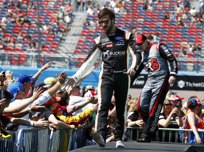 Daniel Suarez is greeted by fans during driver introductions prior to the start of the NASCAR Cup Series auto race at ISM Raceway, Sunday, March 10, 2019, in Avondale, Ariz. (AP Photo/Ralph Freso)