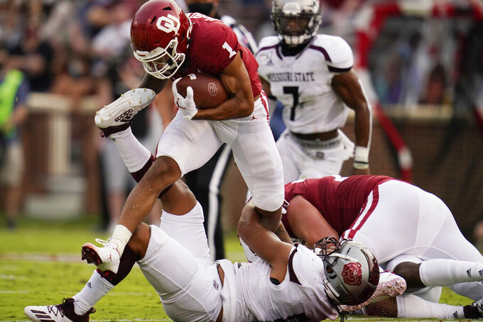 Oklahoma running back Seth McGowan (1) fights off a tackle by Missouri State defender Ferrin Manulelua, bottom, in the first half of an NCAA college football game Saturday, Sept. 12, 2020, in Norman, Okla. (AP Photo/Sue Ogrocki, Pool)