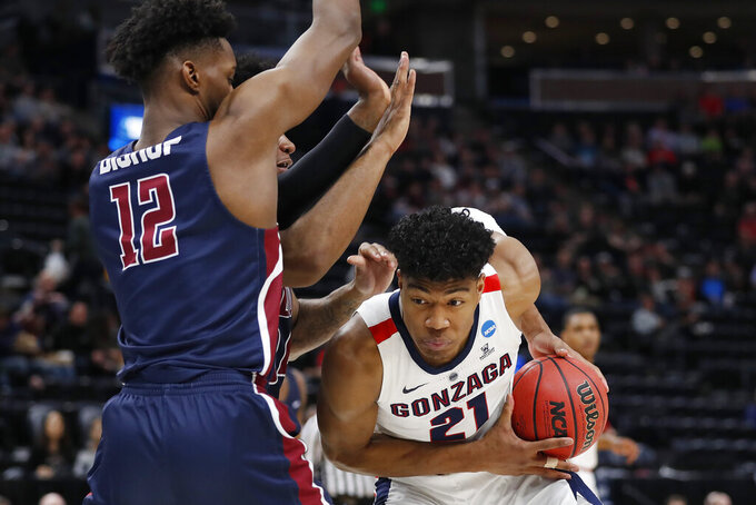 Gonzaga forward Rui Hachimura (21) is defended by Fairleigh Dickinson forwards Mike Holloway Jr., rear, and Kaleb Bishop (12) during the first half of a first-round game in the NCAA men's college basketball tournament Thursday, March 21, 2019, in Salt Lake City. (AP Photo/Jeff Swinger)
