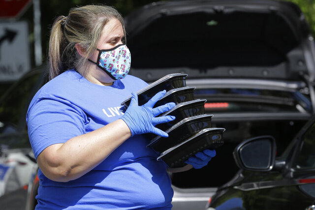 Kristina Ellis prepares to load prepared meals into a vehicle as United Way of Broward County partners with the Miami Dolphins football team to distribute backpacks and meals to military families in need during the coronavirus pandemic, Wednesday, Aug. 5, 2020, in Fort Lauderdale, Fla. (AP Photo/Lynne Sladky)