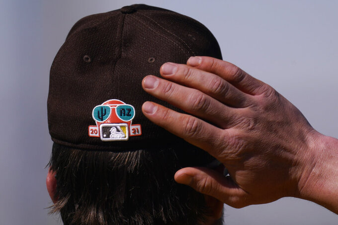San Diego Padres' Wil Myers adjusts his hat with a Cactus League patch during spring training baseball practice Tuesday, Feb. 23, 2021, in Peoria, Ariz. (AP Photo/Charlie Riedel)