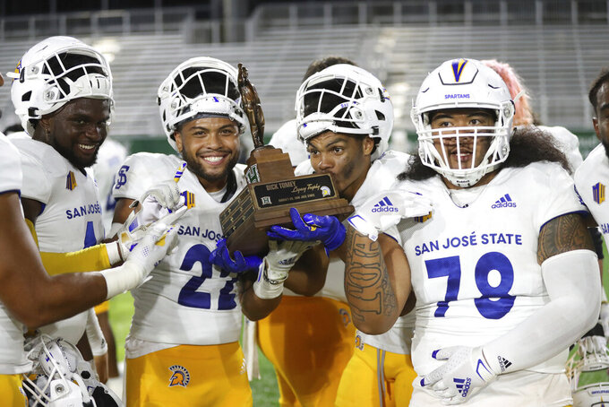 San Jose State players hold the Dick Tomey Legacy trophy after defeating Hawaii 17-13 in an NCAA college football game, Saturday, Sept. 18, 2021, in Honolulu. (AP Photo/Marco Garcia)