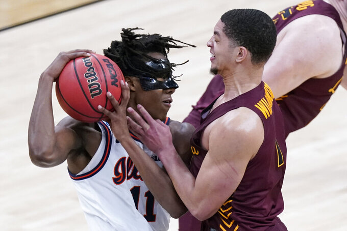Loyola of Chicago's Lucas Williamson (1) defends against Illinois' Ayo Dosunmu (11) during the first half of a college basketball game in the second round of the NCAA tournament at Bankers Life Fieldhouse in Indianapolis Sunday, March 21, 2021. (AP Photo/Mark Humphrey)