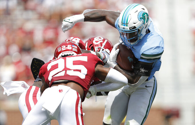 Tulane running back Cameron Carroll (20) works to escape a tackle by Oklahoma defensive back Justin Broiles (25) during an NCAA college football game Saturday, Sept. 4, 2021, in Norman, Okla. (AP Photo/Alonzo Adams)