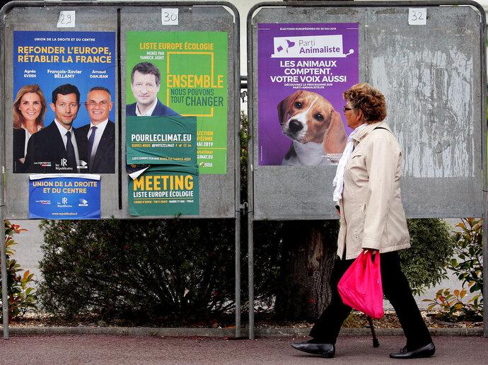 A woman walks past campaign posters for European elections in Saint-Jean-de-Luz, southwestern France, Thursday, May 23, 2019. (AP Photo/Bob Edme)