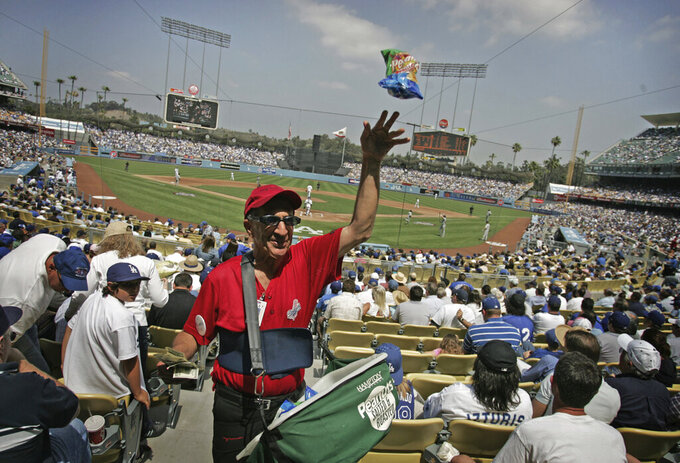 "FILE - In this April 9, 2007, file photo, peanut vendor Richard Aller tosses a bag to a buyer during the Los Angeles Dodgers home opener baseball game against the Colorado Rockies in Los Angeles. Most teams and leagues are reticent to discuss the financial impact from the coronavirus pandemic. There's a loss that's going to take place industry-wise. It's simply unavoidable,"" said Marc Ganis, the co-founder of Chicago-based consulting firm SportsCorp. ""If they can come back, they can reduce the loss for the players, the coaches, the people who work the ticket booths. The ushers, the security people, the parking lot attendants and concessionaires. All of these people — thousands for a football game or baseball game. These are the people that need money, who need to work."" (AP Photo/Branimir Kvartuc, File)"
