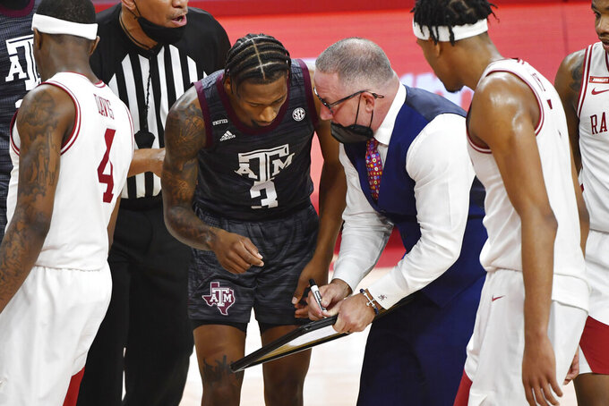 Texas A&M coach Buzz Williams tries to draw out a play with guard Quenton Jackson (3) during a timeout in the second half of an NCAA college basketball game against Arkansas in Fayetteville, Ark., Saturday, March 6, 2021. (AP Photo/Michael Woods)