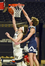 Wake Forest's Ismael Massoud gets past Catawba's Ben Bowen for a layup in an NCAA college basketball game, Thursday, Dec. 31, 2020, at Joel Coliseum in Winston-Salem, N.C. (Walt Unks//The Winston-Salem Journal via AP)