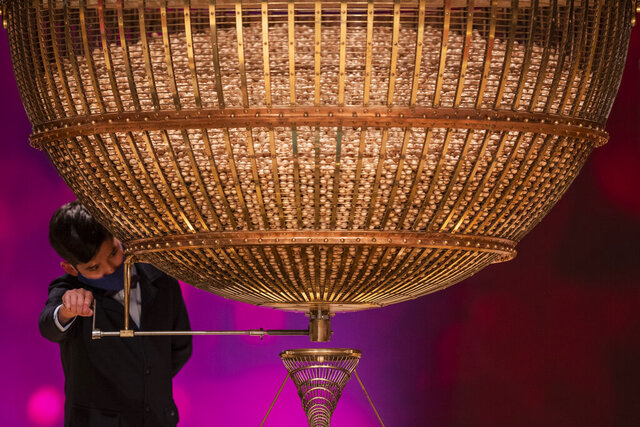 A ball bearing a ticket number falls from a giant drum at Madrid's Teatro Real opera house during Spain's bumper Christmas lottery draw known as El Gordo, or The Fat One, in Madrid, Spain, Tuesday, Dec. 22, 2020. (AP Photo/Bernat Armangue)