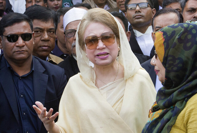 FILE- In this Dec. 28, 2017, file photo, Bangladesh's former prime minister and Bangladesh Nationalist Party (BNP) chairperson Khaleda Zia, center, leaves after a court appearance in Dhaka, Bangladesh. Bangladesh's government said Tuesday, March 24, 2020, it will release Zia, 74 years old, for six months on condition that she stays at home and does not leave the country. (AP Photo/A.M. Ahad, File)