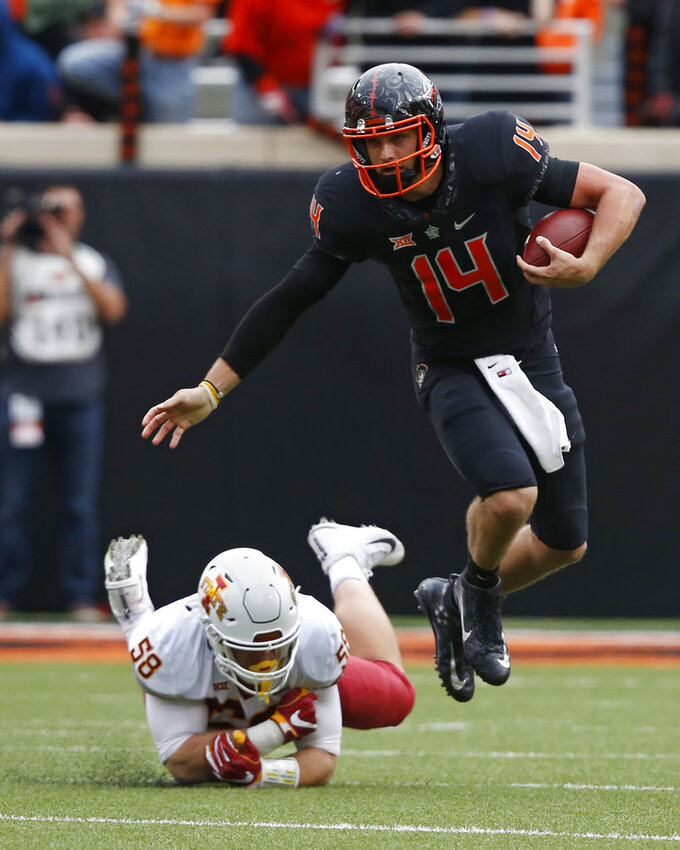Oklahoma State quarterback Taylor Cornelius (14) avoids a tackle by Iowa State defender Spencer Benton (58) in the second half of an NCAA college football game in Stillwater, Okla., Saturday, Oct. 6, 2018. (AP Photo/Sue Ogrocki)