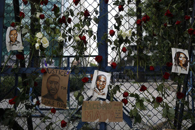 Images of George Floyd, a handcuffed black man who died after being taken into police custody in Minneapolis, hang surrounded by roses on a security barrier outside the U.S. embassy in Mexico City, Saturday, May 30, 2020. A sign in Spanish reads: