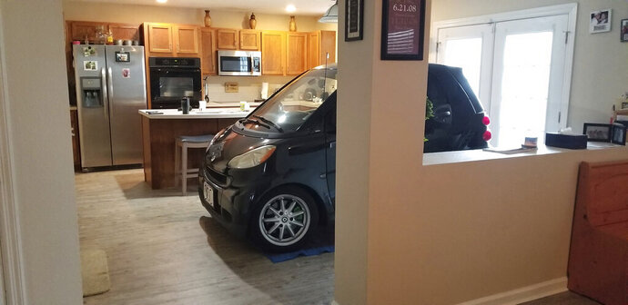 In this Sept. 3, 2019 photo made available by Jessica Eldridge shows her husband's Smart car parked in their kitchen in Jacksonville, Fla. Patrick Eldridge parked his Smart car in his kitchen to protect it from Hurricane Dorian. In a Facebook post, Jessica Eldridge said her husband was