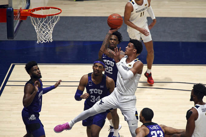 West Virginia forward Jalen Bridges (2) shoots while defended by TCU forward Kevin Easley (34) and guard RJ Nembhard (22) during the first half of an NCAA college basketball game Thursday, March 4, 2021, in Morgantown, W.Va. (AP Photo/Kathleen Batten)