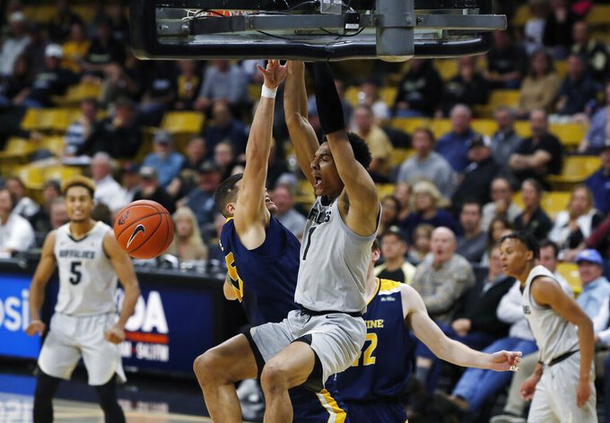 Colorado guard Tyler Bey, front, hangs on the rim after dunking the ball for a basket as UC Irvine center Brad Greene, back left, and forward Tommy Rutherford defend in the second half of an NCAA college basketball game Monday, Nov. 18, 2019, in Boulder, Colo. (AP Photo/David Zalubowski)