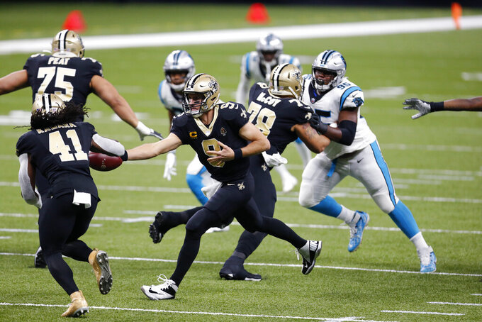 New Orleans Saints quarterback Drew Brees (9) hands off to running back Alvin Kamara (41) in the first half of an NFL football game against the Carolina Panthers in New Orleans, Sunday, Oct. 25, 2020. (AP Photo/Brett Duke)