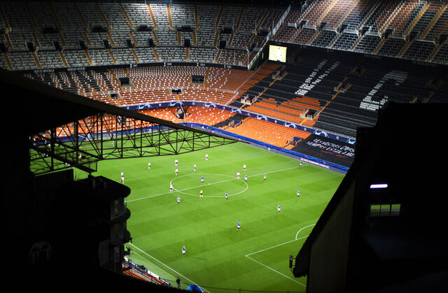 FILE - In this Tuesday March 10, 2020 file photo a general view of the Mestalla stadium during the Champions League round of 16 second leg soccer match between Valencia and Atalanta in Valencia, Spain. The match is being in an empty stadium because of the coronavirus outbreak. All Champions League and Europa League games were postponed by UEFA on Friday March 13, 2020 because of the coronavirus outbreak. For most people, the new coronavirus causes only mild or moderate symptoms, such as fever and cough. For some, especially older adults and people with existing health problems, it can cause more severe illness, including pneumonia. (AP Photo/Emilio Morenatti)