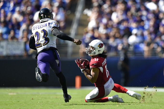 Arizona Cardinals wide receiver Larry Fitzgerald, right, catches a pass in front of Baltimore Ravens strong safety Tony Jefferson in the second half of an NFL football game, Sunday, Sept. 15, 2019, in Baltimore. (AP Photo/Gail Burton)