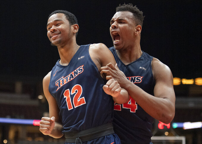 Cal State Fullerton forward Josh Pitts, right, shows his excitement as guard Jamal Smith draws a foul and scored a basket during the second half of an NCAA college basketball game against UC Santa Barbara at the Big West men's tournament in Anaheim, Calif., Friday, March 15, 2019. (AP Photo/Kyusung Gong)