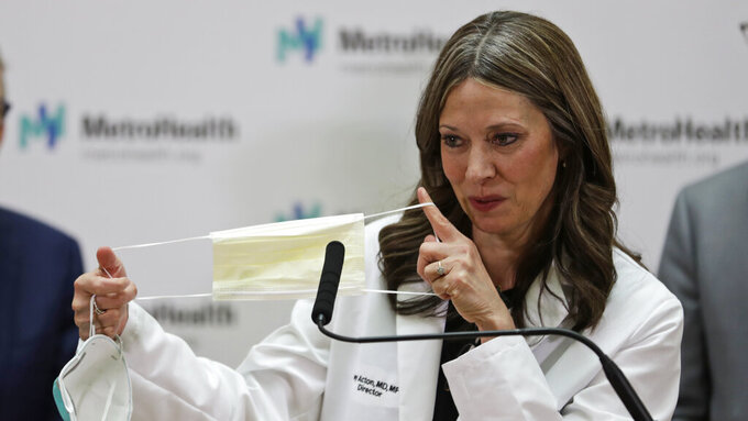 In this Feb. 27, 2020 photo, Ohio Department of Health Director Amy Acton holds up a mask as she gives an update on the state's preparedness and education efforts to limit the potential spread of COVID-19 at MetroHealth Medical Centre  in Cleveland. Dr. Acton has resigned as Ohio's health director, Gov. Mike DeWine said Thursday, June 11, 2020, capping a contentious few months as the target of frustrations during the coronavirus pandemic that included gun-carrying critics showing up at her home. AP Photo/Tony Dejak)