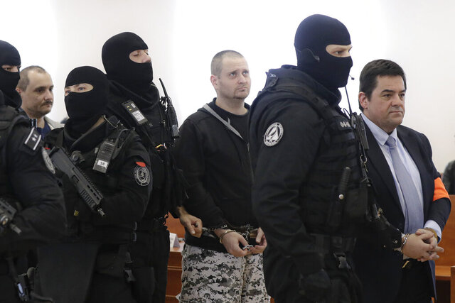 FILE - In this file picture taken on Thursday, Dec. 19, 2019, Marian Kocner, right, the suspected mastermind in the slaying of an investigative journalist Jan Kuciak and his fiancee Martina Kusnirova and suspected shooters Miroslav Marcek, center, and Tomas Szabo, left, are escorted by armed police officers from a courtroom during a trial session in Pezinok, Slovakia. On Monday April 6, 2020. On Wednesday Dec. 2, 2020, an appeals court in Slovakia increased a sentence for Marcek from 23 years to 25 years in prison for the contract killings of an investigative journalist and his fiancee, a case that triggered a political crisis and brought down the country's government. (AP Photo/Petr David Josek/File)