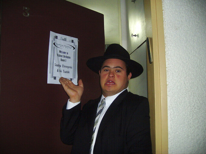 In this Oct. 9, 2006, photo provided by Yaelle Ehrenpreis Meyer, Saadya Ehrenpreis points to the sign displayed on his hotel room door during Yeshivat Darkaynu, a program for special needs young men, in Alon Shvut, Israel. (Yaelle Ehrenpreis Meyer via AP)