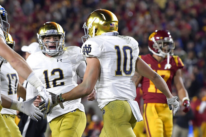 Notre Dame wide receiver Chris Finke, foreground, celebrates his touchdown with quarterback Ian Book (12) during the first half of an NCAA college football game against Southern California on Saturday, Nov. 24, 2018, in Los Angeles. (AP Photo/Mark J. Terrill)