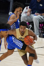 Georgia Tech guard Kyle Sturdivant (1) works to get around Kentucky forward Olivier Sarr, top, during the second half of an NCAA college basketball game Sunday, Dec. 6, 2020, in Atlanta. (AP Photo/John Bazemore)