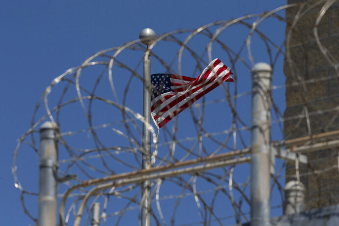 FILE - In this April 17, 2019 file photo reviewed by U.S. military officials, a U.S. flag flies inside the razor wire of the Camp VI detention facility, Wednesday, April 17, 2019, in Guantanamo Bay Naval Base, Cuba. (AP Photo/Alex Brandon)