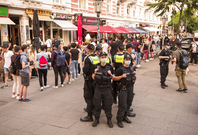 """Police officers stand in the evening in the Schanzenviertel on the street """"Schulterblatt"""" and control the coronavirus rules, in Hamburg, Germany, Friday, June 4, 2021. In the Schanzenviertel, alcohol may no longer be served outside on the weekend. (Daniel Bockwoldt/dpa via AP)"""