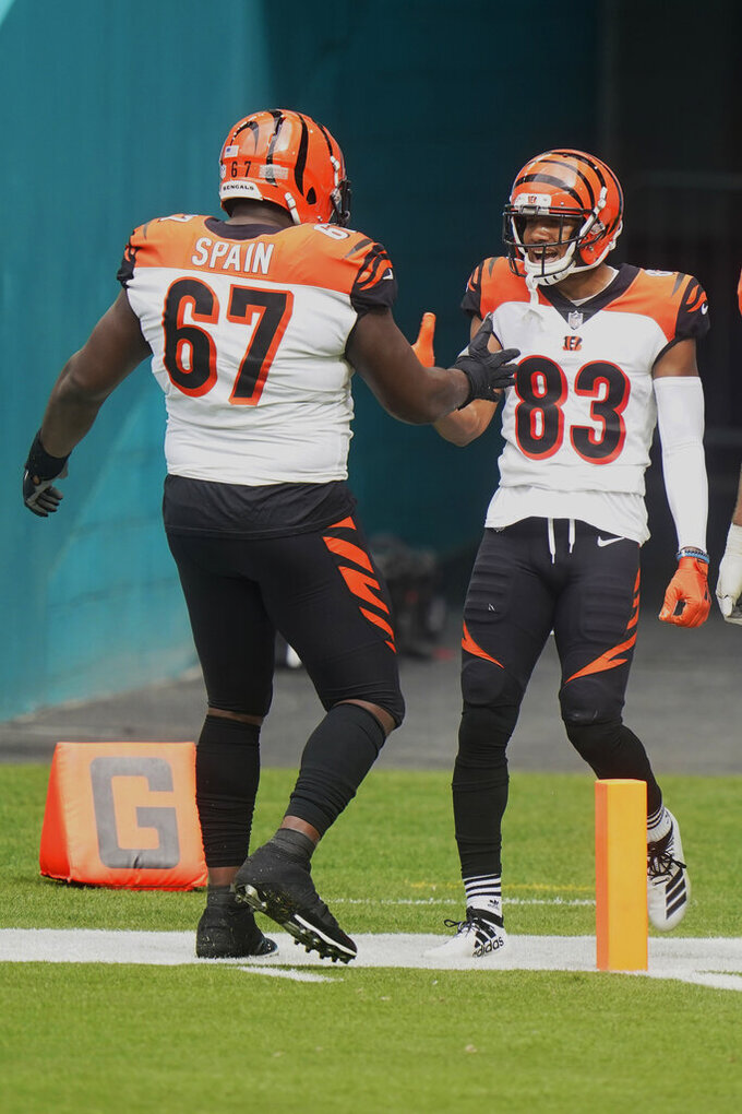 Cincinnati Bengals offensive guard Quinton Spain (67) congratulates wide receiver Tyler Boyd (83) after Boyd scored a touchdown during the first half of an NFL football game against the Miami Dolphins, Sunday, Dec. 6, 2020, in Miami Gardens, Fla. (AP Photo/Wilfredo Lee)