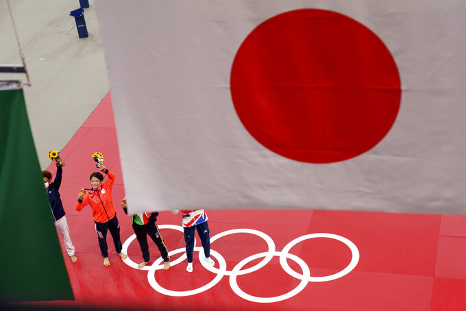 """FILE - In this July 25, 2021, file photo, Gold medalist Uta Abe, of Japan, second from left, stands beneath her country's flag following the medal ceremony for women's -52kg judo, at the 2020 Summer Olympics, Sunday, July 25, 2021, in Tokyo. When the Tokyo Olympics began during a worsening pandemic, the majority of the host nation was in opposition, with Emperor Naruhito dropping the word """"celebrating"""" from his opening declaration of welcome. But once the Games got underway and local media switched to covering Japanese athletes' """"medal rush,"""" many were won over. (AP Photo/David Goldman, File)"""