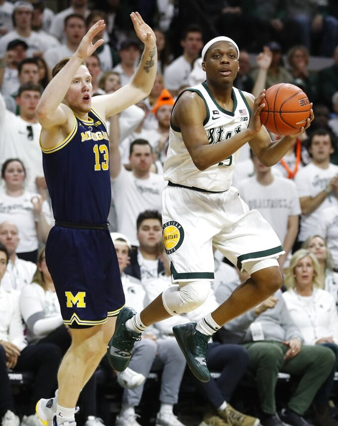 Michigan State guard Cassius Winston (5) passes the ball as Michigan forward Ignas Brazdeikis (13) defends during the first half of an NCAA college basketball game Saturday, March 9, 2019, in East Lansing, Mich. (AP Photo/Carlos Osorio)