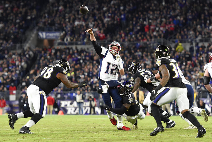 New England Patriots quarterback Tom Brady (12) attempts a pass as Baltimore Ravens linebacker Matthew Judon (99) makes a hit during the first half of an NFL football game, Sunday, Nov. 3, 2019, in Baltimore. The pass was incomplete. (AP Photo/Gail Burton)