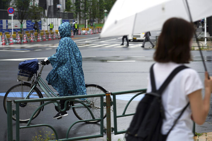 A woman wearing a protective mask to help curb the spread of the coronavirus rides a bicycle in the rain Monday, June 14, 2021, in Tokyo. Japan is desperately pushing to accelerate the pace of inoculations before the Tokyo Olympics. (AP Photo/Eugene Hoshiko)