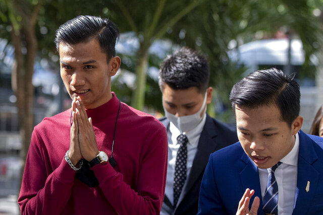 Pro-democracy activist Panupong Jadnok, also known as Mike Rayong, left, greets as he arrives at criminal courthouse for hearing to determine whether he has violated his bail conditions in Bangkok, Thailand, Thursday, Sept. 3, 2020. Growing pro-democracy protests have emerged as the most serious threat to the government led by a former army general accused of incompetence and corruption by protesters. (AP Photo/Gemunu Amarasinghe)